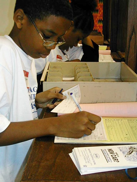 A young man writes a receipt as part of Seaway's commitment to educate youth on financial issues.