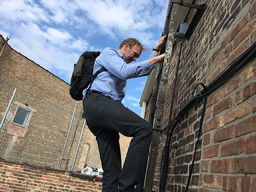 Videographer climbs a building in Chicago to get a shot for this documentary project.